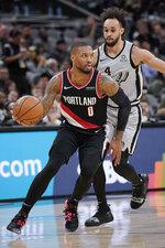 Portland Trail Blazers' Damian Lillard (0) evades San Antonio Spurs' Derrick White during the first half of an NBA basketball game, Saturday, Nov. 16, 2019, in San Antonio. (AP Photo/Darren Abate)