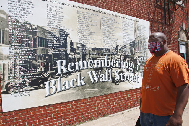 Freeman Culver stands in front of a mural listing the names of businesses destroyed during the Tulsa race massacre in Tulsa, Okla., Monday, June 15, 2020, on the other side of what's historically the city's white-black dividing line from where President Donald Trump will rally Saturday. (AP Photo/Sue Ogrocki)