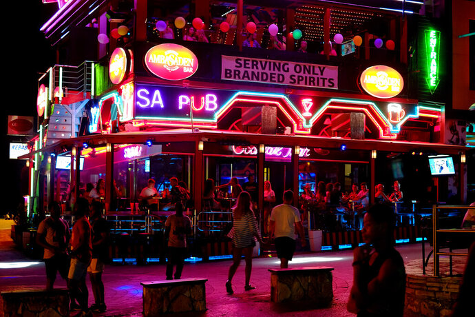 Tourist enjoy their drinks in a pub as other walk in southeast resort of Ayia Napa in the east Mediterranean island of Cyprus late Wednesday, July 17, 2019. A Cyprus police official says 12 Israelis have been detained after a 19-year-old British woman alleged that she was raped in the resort town of Ayia Napa. (AP Photo/Petros Karadjias)