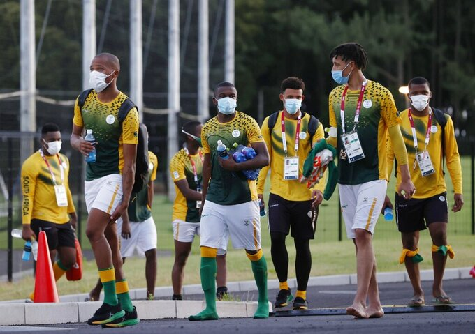 South Africa's Olympic soccer team members, wearing face masks, leave the training venue in Chiba, east of Tokyo, Monday, July 19, 2021. Two South African soccer players have become the first athletes inside the Olympic Village to test positive for COVID-19. The Tokyo Games open on Friday.  (Kyodo News via AP)