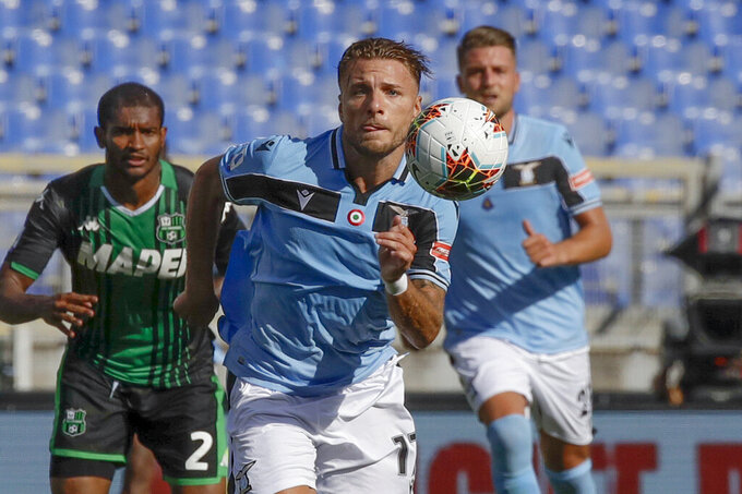 """FILE - In this Saturday, July 11, 2020 file photo, Lazio's Ciro Immobile eyes the ball during the Serie A soccer match between Lazio and Sassuolo at the Rome Olympic Stadium. Prolific scorer Ciro Immobile has extended his contract with Lazio through 2025. His previous contract was due to expire in 2023.""""This is important, because Immobile had gained the attention of some big clubs, considering that he's the European Golden Shoe holder,"""" Lazio communications director Stefano De Martino said Monday. (AP Photo/Alessandra Tarantino, File)"""