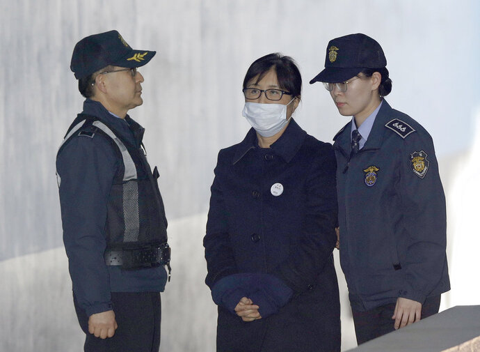 Choi Soon-sil, center, a confidante of former South Korean President Park Geun-hye, arrives at the Seoul Central District Court in Seoul, South Korea, Tuesday, Feb. 13, 2018. Choi Soon-sil, a confidante of former South Korean President Park Guen-hye has arrived at court to hear the verdict in her political corruption case. (AP Photo/Ahn Young-joon)