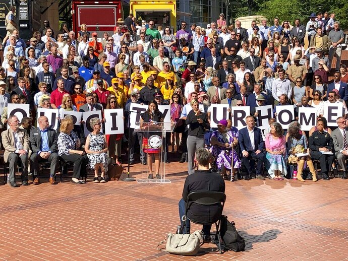 Members of dozens of civic leaders hold up signs spelling out Our City Our Home on Wednesday, Aug. 14, 2019, in Portland, Ore., during a rally to support the city in advance of protests planned for Saturday. The Mayor of Portland, Ted Wheeler, said anyone planning violence or espousing hatred at an upcoming weekend protest by right-wing groups in the liberal city