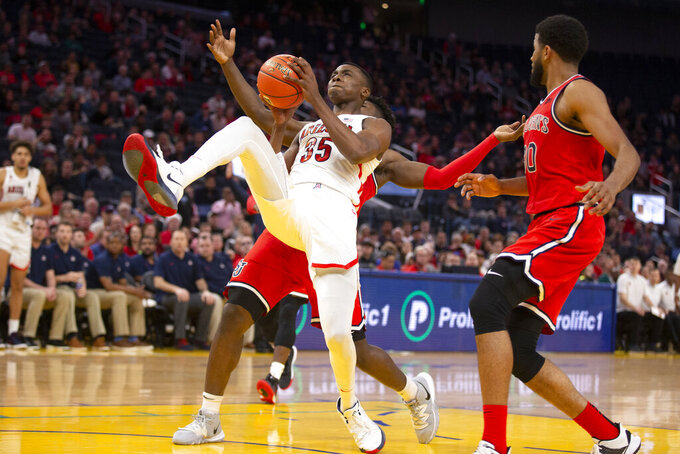 Arizona center Christian Koloko (35) is fouled by St. John's forward Marcellus Earlington, back left, during the second half of an NCAA college basketball game Saturday, Dec. 21, 2019, in San Francisco. St. John's defeated Arizona 70-67. (AP Photo/D. Ross Cameron)