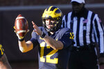 Michigan quarterback Cade McNamara takes the snap during the second half of an NCAA college football game against Penn State, Saturday, Nov. 28, 2020, in Ann Arbor, Mich. (AP Photo/Carlos Osorio)