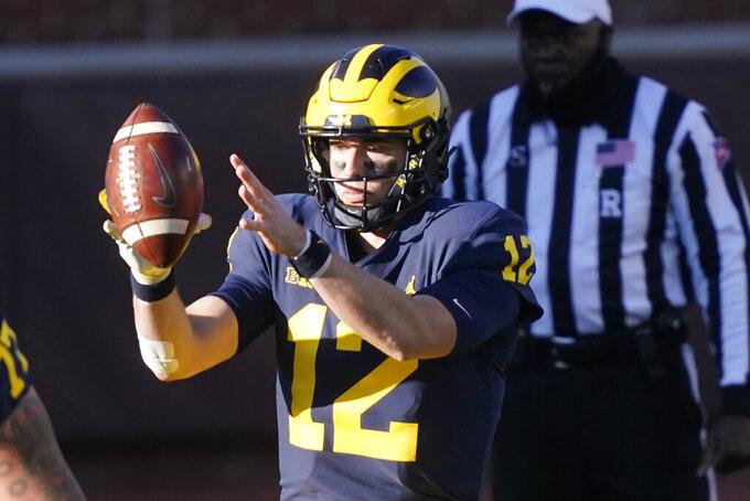 Michigan quarterback Cade McNamara takes the snap during the second half of an NCAA college football game against Penn State, Saturday, Nov. 28, 2020, in Ann Arbor, Mich. (AP Photo/Carlos Osorio)