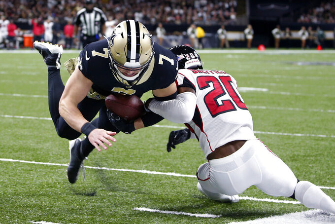 New Orleans Saints quarterback Taysom Hill (7) is tackled near the end zone pylon by Atlanta Falcons defensive back Kendall Sheffield (20) in the first half of an NFL football game in New Orleans, Sunday, Nov. 10, 2019. (AP Photo/Butch Dill)
