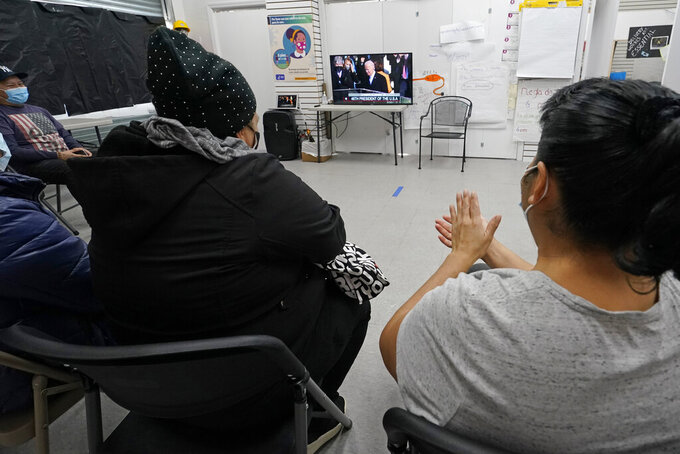 Blanca Cedillos, left, a nanny, and Graciela Uraga, right, a cleaning lady, applaud as they watch the inauguration of President Joe Biden on TV with other immigrants at the Workers Justice Center, a Brooklyn non-rpofit that helps immigrants, Wednesday, Jan. 20, 2021, in the Sunset Park neighborhood of Brooklyn in New York. (AP Photo/Kathy Willens)