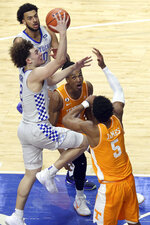 Kentucky's Devin Askew, left, shoots as Tennessee's Yves Pons, middle, and Josiah-Jordan James (5) defend during the second half of an NCAA college basketball game in Lexington, Ky., Saturday, Feb. 6, 2021. (AP Photo/James Crisp)