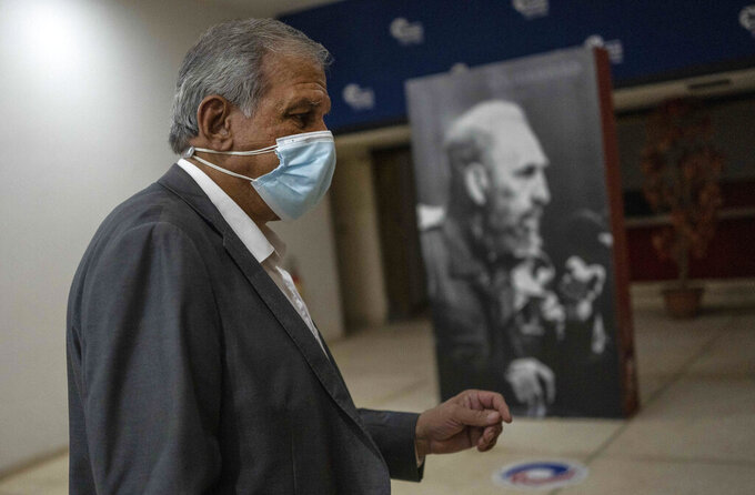 """Mitchell Joseph Valdes Sosa, the director of the Cuban Neurosciences Center, walks past a photo of Fidel Castro before a press conference about symptoms reported by U.S. and Canadian diplomats  in 2016 and 2017, commonly referred to as the """"Havana Syndrome,"""" in Havana, Cuba, Monday, Sept. 13, 2021. (AP Photo/Ramon Espinosa)"""