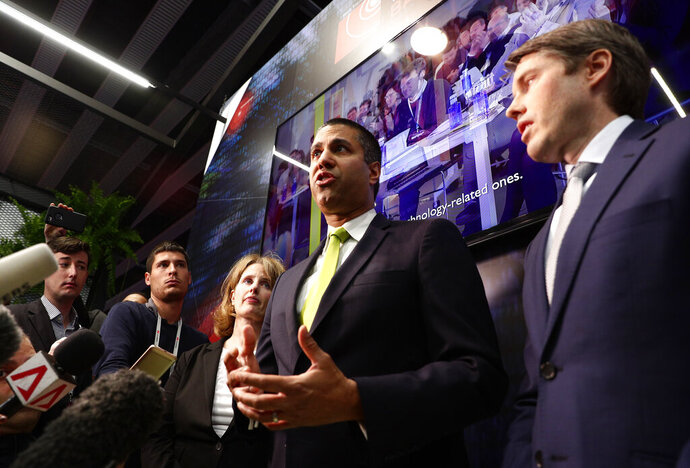 U.S. Deputy Assistant secretary for Cyber and International Communications and Information Policy Robert Strayer, right, and Ajit Pai, chairman of the Federal Communications Commission, centre, attend a press conference at the Mobile World Congress wireless show, in Barcelona, Spain, Tuesday, Feb. 26, 2019. The annual Mobile World Congress (MWC) runs from 25-28 February in Barcelona, where companies from all over the world gather to share new products. (AP Photo/Manu Fernandez)