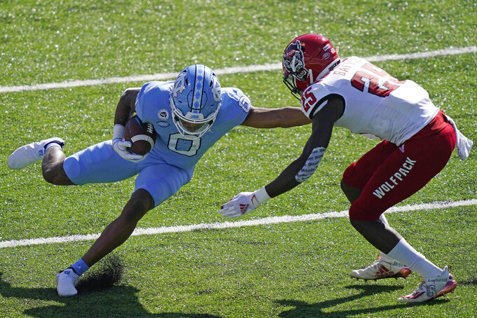 North Carolina wide receiver Emery Simmons (0) runs the ball while North Carolina State cornerback Shyheim Battle (25) looks to tackle during the first half of an NCAA college football game in Chapel Hill, N.C., Saturday, Oct. 24, 2020. (AP Photo/Gerry Broome)