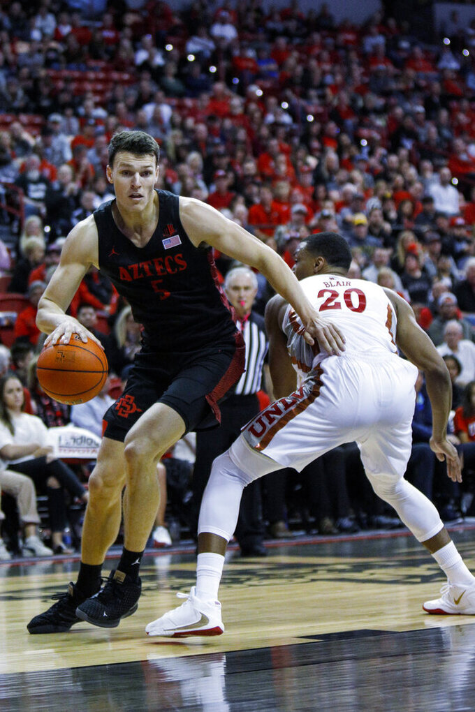 San Diego State's Yanni Wetzell (5) drives to the rim against UNLV's Nick Blair (20) during the second half of an NCAA college basketball game on Sunday, Jan. 26, 2020, in Las Vegas. (AP Photo/Joe Buglewicz)