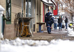 U.S. Postal Service mail carrier Tereasa Clarkson makes deliveries downtown on a windy and snowy morning in Greeley, Colo., Saturday, Nov. 30, 2019. The weather caused the city to cancel its annual Greeley Lights the Night parade, which was scheduled in the evening. (Alex McIntyre/The Greeley Tribune via AP)