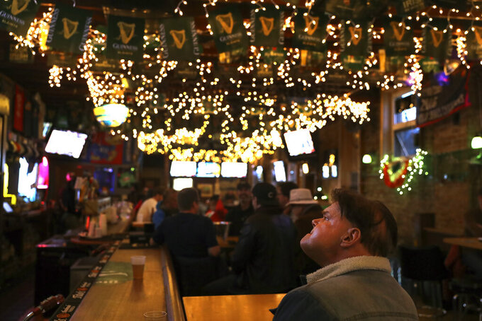Lights hang from the ceiling of Lottie's Pub in Chicago's Bucktown neighborhood as Cliff Naumann watches one of the many television screens Saturday, March 13, 2021. Bars and restaurants are going to see something this week that they haven't seen in two years: Fans on barstools watching their favorite teams. (AP Photo/Shafkat Anowar)