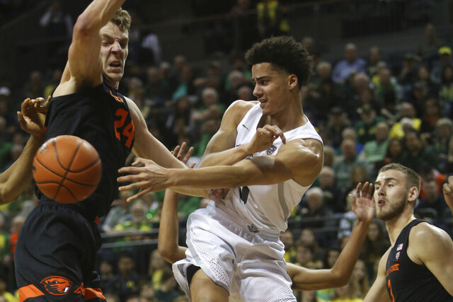 Oregon's Will Richardson, center, passes the ball between Oregon State's Kylor Kelley, left, and Tres Tinkle, right, during the first half of an NCAA college basketball game in Eugene, Ore., Thursday, Feb. 27, 2020. (AP Photo/Chris Pietsch)