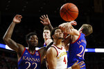 Iowa State forward George Conditt IV, center, fights for a rebound with Kansas' Silvio De Sousa, left, and Michael Jankovich, right, during the second half of an NCAA college basketball game Wednesday, Jan. 8, 2020, in Ames, Iowa. Kansas won 79-53. (AP Photo/Charlie Neibergall)