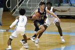 Notre Dame forward Nate Laszewski (14) drives between North Carolina guard Leaky Black (1) and forward Day'Ron Sharpe (11) during the first half of an NCAA college basketball game in Chapel Hill, N.C., Saturday, Jan. 2, 2021. (AP Photo/Gerry Broome)