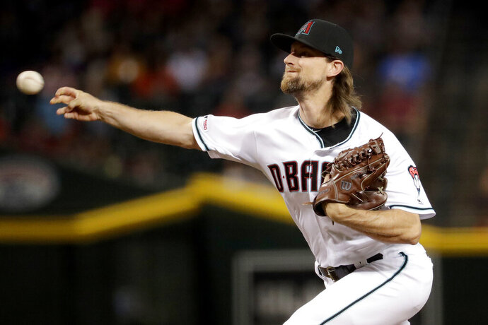 FILE - In this Sept. 24, 2019, file photo, Arizona Diamondbacks starting pitcher Mike Leake throws against the St. Louis Cardinals during the first inning of a baseball game, in Phoenix. Diamondbacks right-hander Mike Leake has opted out of the 2020 season due to concerns about the coronavirus. Diamondbacks general manager Mike Hazen did not elaborate on Leake's decision during a Zoom call, but the pitcher's agent issued a statement saying he made a personal decision not to play during the pandemic. (AP Photo/Matt York, File)