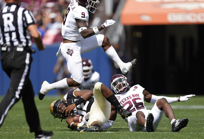 Texas A&M defensive back Demani Richardson, right, and defensive back Leon O'Neal Jr., top, bring down Colorado quarterback Brendon Lewis after a short gain in the first half of an NCAA college football game, Saturday, Sept. 11, 2021, in Denver. (AP Photo/David Zalubowski)