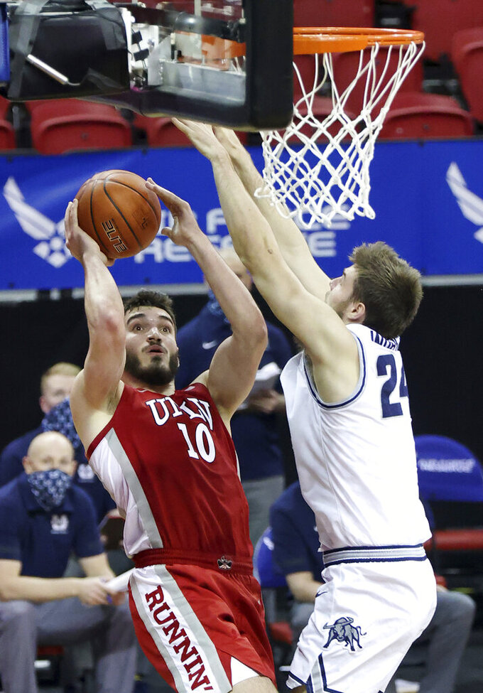 UNLV forward Edoardo Del Cadia (10) shoots as Utah State guard Rollie Worster (24) defends during the first half of an NCAA college basketball game in the quarterfinals of the Mountain West Conference men's tournament Thursday, March 11, 2021, in Las Vegas. (AP Photo/Isaac Brekken)