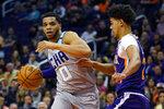 Charlotte Hornets forward Miles Bridges (0) drives on Phoenix Suns forward Cameron Johnson during the first half of an NBA basketball game Sunday, Jan. 12, 2020, in Phoenix. (AP Photo/Rick Scuteri)