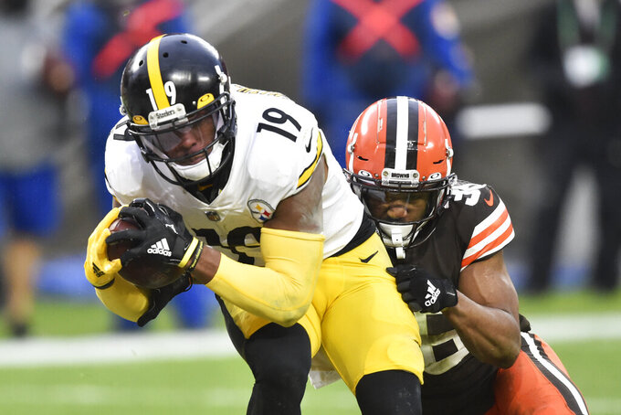 Pittsburgh Steelers wide receiver JuJu Smith-Schuster (19) catches a 2-yard touchdown pass under pressure from Cleveland Browns cornerback M.J. Stewart Jr. (36) during the second half of an NFL football game, Sunday, Jan. 3, 2021, in Cleveland. (AP Photo/David Richard)