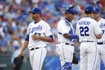 Kansas City Royals pitcher Carlos Hernandez, left, walks to the dugout after being taken out in the fourth inning of a baseball game against the Detroit Tigers at Kauffman Stadium in Kansas City, Mo., Saturday, July 24, 2021. Royals manager Mike Matheny (22) catcher Salvador Perez, second from left, and third baseman Hunter Dozier, right, stand on the mound. (AP Photo/Colin E. Braley)