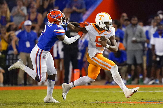Tennessee quarterback Hendon Hooker (5) scrambles as he tries to get past Florida linebacker Amari Burney (2) during the first half of an NCAA college football game, Saturday, Sept. 25, 2021, in Gainesville, Fla. (AP Photo/John Raoux)