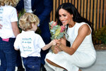 Meghan the Duchess of Sussex receives native flowers from 4-year-old Findlay Blue after she and Prince Harry officially opened the Taronga Institute of Science and Learning at Taronga Zoo in Sydney, Australia, Tuesday, Oct. 16, 2018. Prince Harry and his wife Meghan are on a 16-day tour of Australia and the South Pacific.(Peter Parks/Pool via AP)