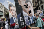 Demonstrators hold posters showing French Interior Minister Gerald Darmanin during a demonstration, Saturday, June 12, 2021 in Paris. Thousands of people rallied throughout France Saturday to protest against the far-right. (AP Photo/Lewis Joly)