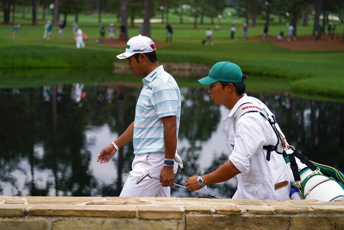 Hideki Matsuyama, of Japan, walks on the 15th hole with his caddie Shota Hayafuji during the third round of the Masters golf tournament on Saturday, April 10, 2021, in Augusta, Ga. (AP Photo/Matt Slocum)