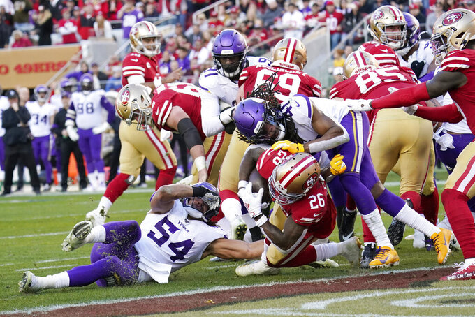 San Francisco 49ers running back Tevin Coleman (26) dives to score a touchdown between Minnesota Vikings middle linebacker Eric Kendricks (54) and defensive back Anthony Harris (41) during the second half of an NFL divisional playoff football game, Saturday, Jan. 11, 2020, in Santa Clara, Calif. (AP Photo/Tony Avelar)