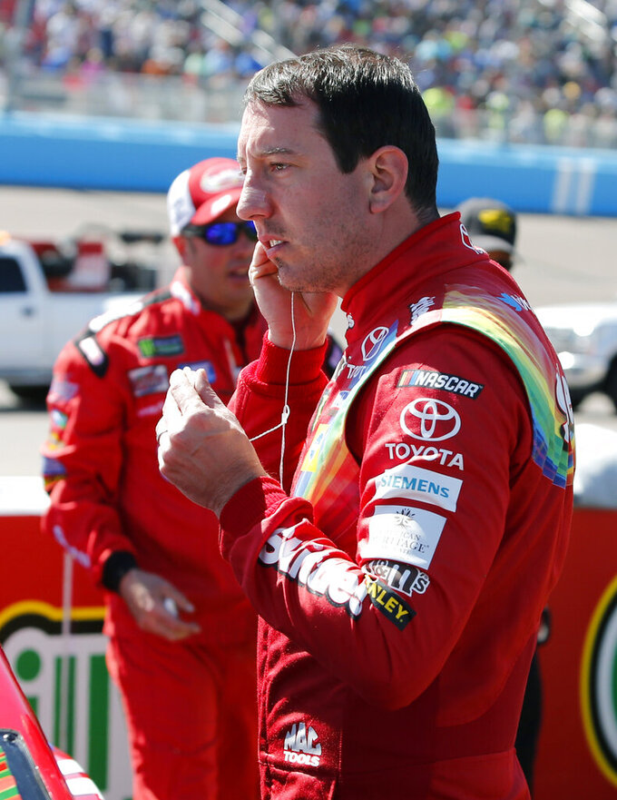 Kyle Busch prepares to enter his race car prior to the start of the NASCAR Cup Series auto race at ISM Raceway, Sunday, March 10, 2019, in Avondale, Ariz. (AP Photo/Ralph Freso)