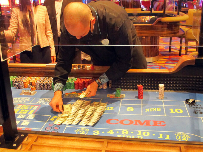 A dealer counts money at a craps table at the Hard Rock casino in Atlantic City , N.J., on May 3, 2021. Figures released May 14, 2021, show Atlantic City's casinos won nearly four times as much from gamblers in April as they did a year ago, when the casinos were closed, and online betting was the only game in town. (AP Photo/Wayne Parry)