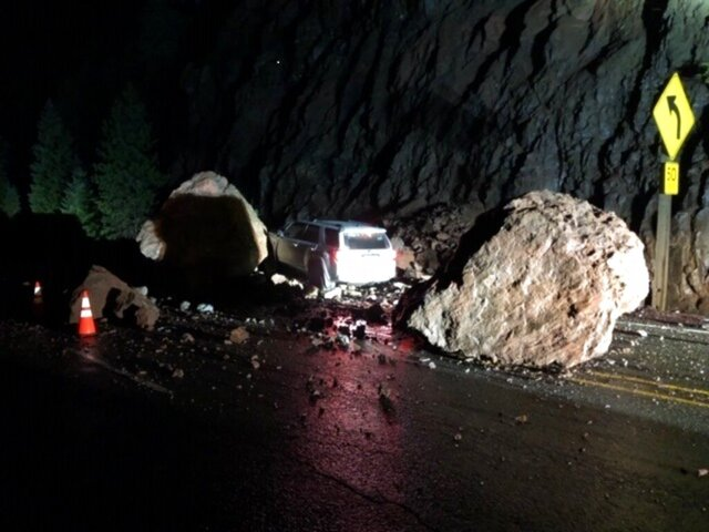 This photo provided by The Oregon Department of Transportation shows two enormous boulders that fell onto Highway 62, almost crushing a car outside of Prospect, Ore. on Tuesday, Jan. 28, 2020. The unrelenting rain around Oregon this week is having an impact, with multiple roads and highways closed around the state due to flooding and rockslides. Officials in Yamhill County said a driver was rescued from a flooded vehicle Tuesday morning near Amity after the car stalled in about a foot of water and some local roads in Washington County were closed due to flooding. (The Oregon Department of Transportation via AP)
