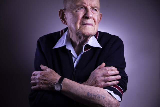In this Thursday, Dec. 12, 2019 photo, Mordechai Ciechanower, a 95-year-old Auschwitz survivor, shows his tattooed identification number as poses for a photo at his home in Ramat Gan, Israel. His mother and two sisters were killed upon arrival in Auschwitz and he says he survived his nearly two years in the camp thanks to his roofing skills and the generous help of others.