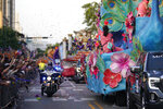 """Police ride between crowds and floats during a parade dubbed """"Tardy Gras,"""" to compensate for a cancelled Mardi Gras due to the COVID-19 pandemic, in Mobile, Ala., Friday, May 21, 2021. (AP Photo/Gerald Herbert)"""