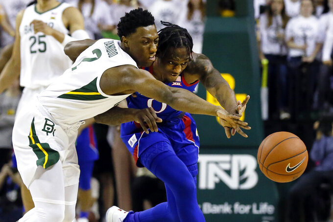 Baylor guard Devonte Bandoo, left, and Kansas guard Marcus Garrett, right, reach for the loose ball during the first half of an NCAA college basketball game on Saturday, Feb. 22, 2020, in Waco, Texas. (AP Photo/Ray Carlin)