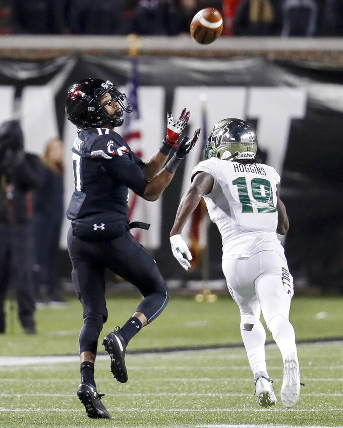 Cincinnati wide receiver Rashad Medaris (17) catches a pass against South Florida cornerback Ronnie Hoggins (19) during the second half of an NCAA college football game, Saturday, Nov. 10, 2018, in Cincinnati. (AP Photo/John Minchillo)