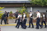 Cadets at the Washington state Criminal Justice Training Commission, walk past a training exercise in progress, Wednesday, July 14, 2021, in Burien, Wash. Washington state is embarking on a massive experiment in police reform and accountability following the racial justice protests that erupted after George Floyd's murder last year, with nearly a dozen new laws that took effect Sunday, July 25, but law enforcement officials remain uncertain about what they require in how officers might respond — or not respond — to certain situations, including active crime scenes and mental health crises. (AP Photo/Ted S. Warren)