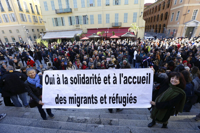 This Jan. 4, 2017 photo shows a crowd supporting Cedric Herrou, a French activist farmer accused of helping African migrants to cross the border from Italy, in Nice, southern France. The banner reads
