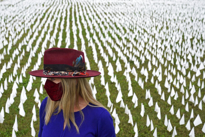 """Artist Suzanne Brennan Firstenberg stands among thousands of white flags planted in remembrance of Americans who have died of COVID-19, Tuesday, Oct. 27, 2020, near Robert F. Kennedy Memorial Stadium in Washington. Firstenberg's temporary art installation, called """"In America, How Could This Happen,"""" will include an estimated 240,000 flags when completed. (AP Photo/Patrick Semansky)"""