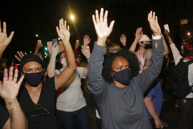 Protesters hold their hands in the air in the Brooklyn borough of New York, Saturday, May 30, 2020. Demonstrators took to the streets of New York City to protest the death of George Floyd, a black man who was killed in police custody in Minneapolis on May 25. (AP Photo/Seth Wenig)