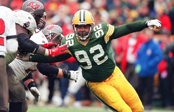 FILE - In this Jan. 4, 1998, file photo, Green Bay Packers Reggie White moves in on the Tampa Bay defense in the NFC Divisional Playoff game in Green Bay, Wis. The NFL wouldn't be the gigantic force it is in society and sports today without free agency empowering most players with freedom and fortune and endowing most long-suffering franchises and their fans with hope. The first offseason featuring modern free agency was in 1993, and it produced the most significant free agent signing in NFL history: Reggie White (AP Photo/Charles Krupa, File)