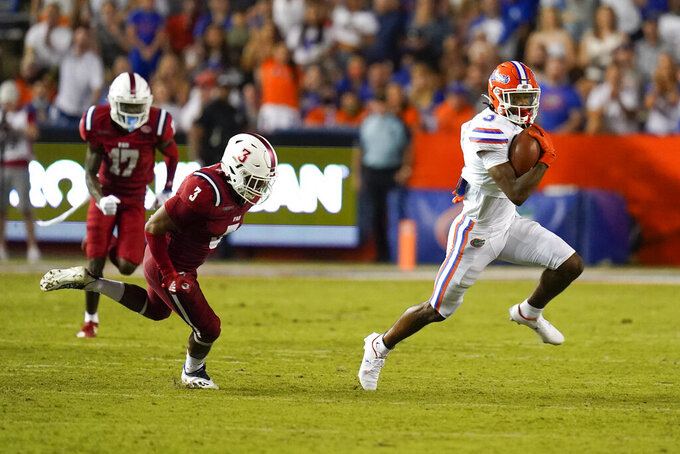 Florida's Xzavier Henderson returns a punt as he gets past Florida Atlantic linebacker Eddie Williams (3) and safety Yanez Rogers (17) during the second half of an NCAA college football game Saturday, Sept. 4, 2021, in Gainesville, Fla. (AP Photo/John Raoux)
