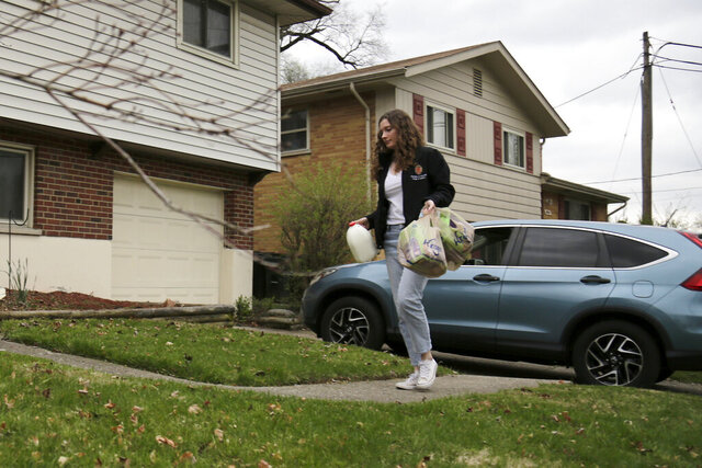 FILE—This file photo from March 31, 2020 shows Alyssa Kelder, a medical school student at the University of Cincinnati, as she delivers groceries to the home of Yvonne Carrell, in the Finneytown neighborhood of Cincinnati. Aspiring doctors in Cincinnati whose studies were interrupted by the coronavirus outbreak have found a new mission of mercy. University of Cincinnati medical students started a