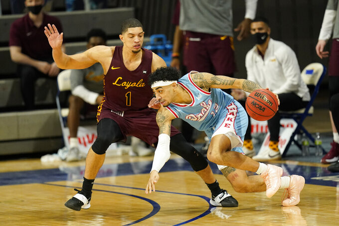 Drake guard Roman Penn drives past Loyola of Chicago guard Lucas Williamson (1) during the first half of an NCAA college basketball game, Saturday, Feb. 13, 2021, in Des Moines, Iowa. (AP Photo/Charlie Neibergall)