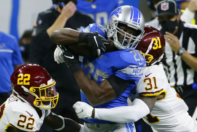 Detroit Lions running back Adrian Peterson (28) is stopped by Washington Football Team safeties Deshazor Everett (22) and Kamren Curl (31) during the first half of an NFL football game, Sunday, Nov. 15, 2020, in Detroit. (AP Photo/Duane Burleson)