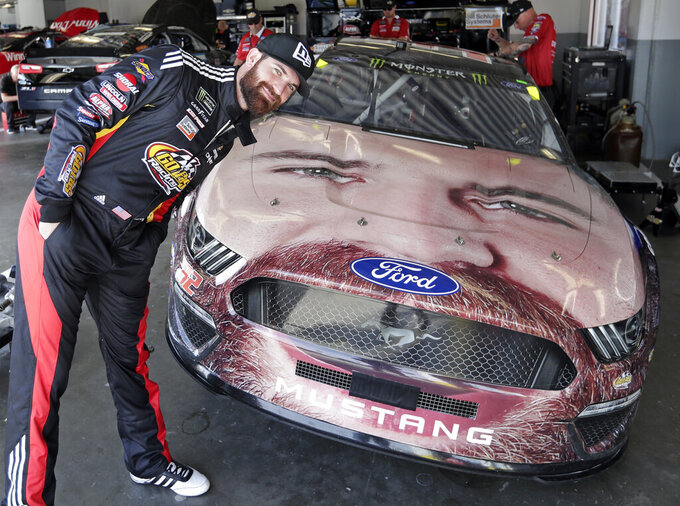 Corey LaJoie leans over the hood of his car with a likeness of him painted on the front end before a practice session for the NASCAR Daytona 500 auto race at Daytona International Speedway, Friday, Feb. 15, 2019, in Daytona Beach, Fla. (AP Photo/John Raoux)
